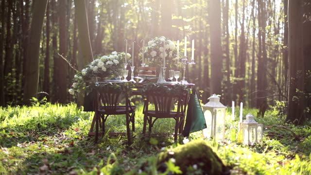 vídeos de stock, filmes e b-roll de decoração de casamento na natureza na floresta. decoração de casamento em tons de chocolate. bolo de chocolate em casamento mesa com flores na floresta. - rústico