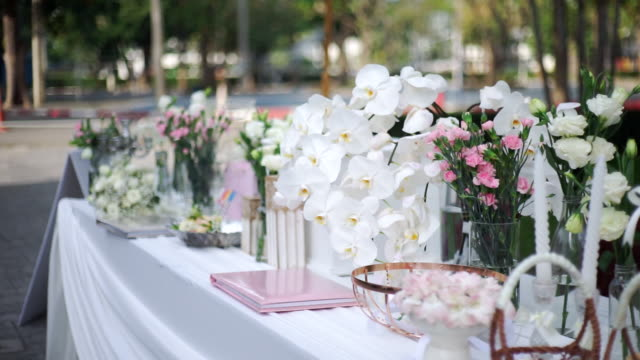Wedding decoration with various of flower bouquets on the table outdoors.