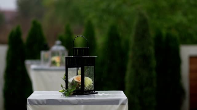 wedding decorations in rustic style. flowers in lantern on the wedding ceremony outdoors on rainy day - wedding fashion stock videos and b-roll footage
