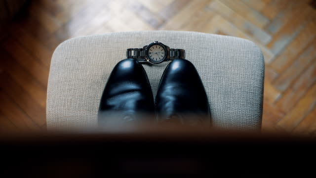 wedding details. grooms wedding shoes and clock on a chair - личный аксессуар стоковые видео и кадры b-roll