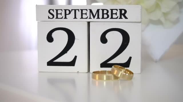 vídeos de stock e filmes b-roll de wedding gold rings lie on a table - setembro