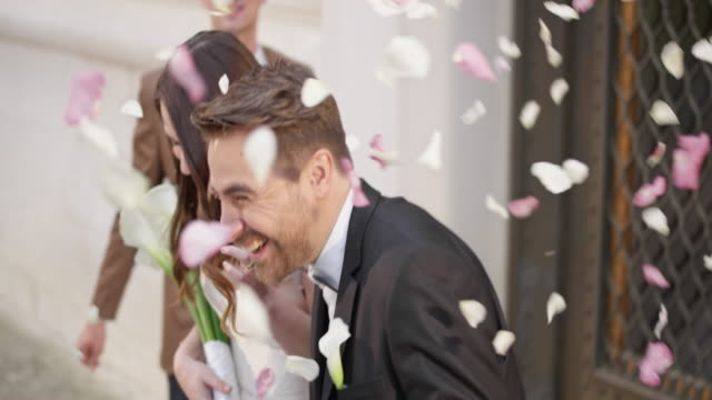 SLO MO DS Wedding guests showering newlyweds with rose petals
