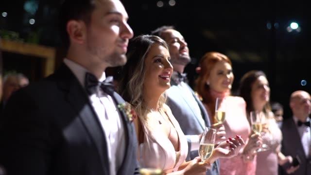 vidéos et rushes de invités de mariage souriant et retenant une boisson - soirées habillées
