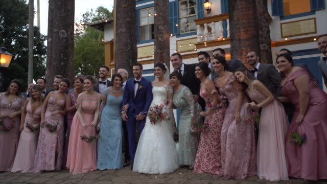 wedding guests taking a picture with the bride and groom - young couple wedding friends video stock e b–roll