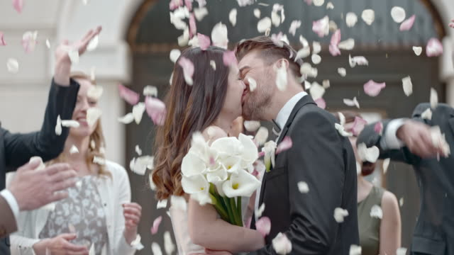 slo mo wedding guests throwing petals at kissing newlyweds - matrimonio video stock e b–roll