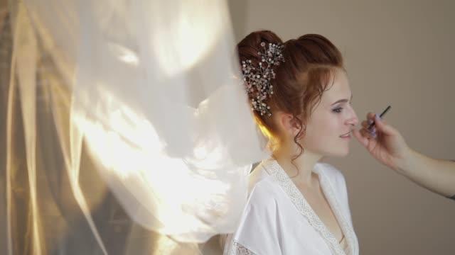 """vídeos de stock, filmes e b-roll de o artista da composição do casamento que faz um make up para a noiva no véu. modelo """"sexy"""" bonito - moda de casamento"""