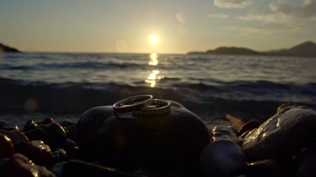 Wedding Rings by the sea at sunset Wedding Rings by the sea at sunset brushed metal stock videos & royalty-free footage