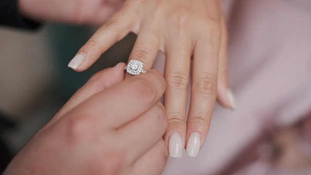 vídeos de stock e filmes b-roll de wedding rings. guy put the ring on the girl's finger. - jóias