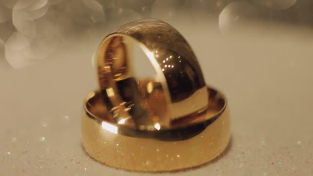 Wedding rings lying on shiny surface shining with light close up macro