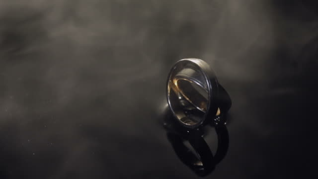 Wedding rings on dark water surface shining with light. Close up macro. Rings in water pair. Reflection. Slow motion