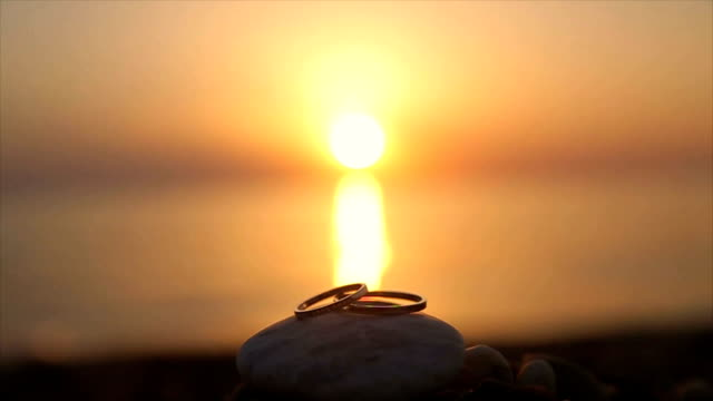 Wedding rings on the beach at sunset,romantic and love concept Wedding rings on the beach at sunset,romantic and love concept eternity stock videos & royalty-free footage