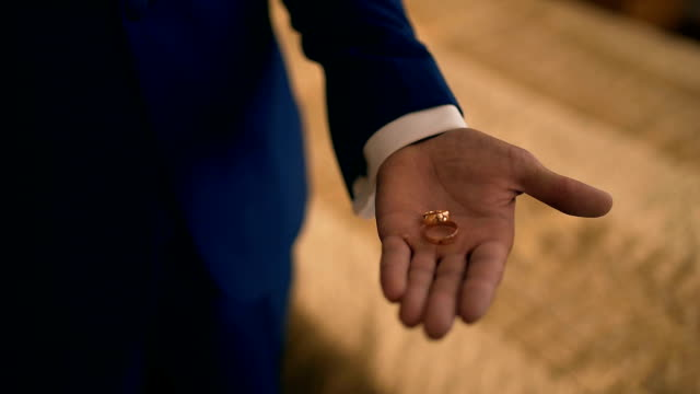 Wedding rings on the palm of the groom, marriage proposal video