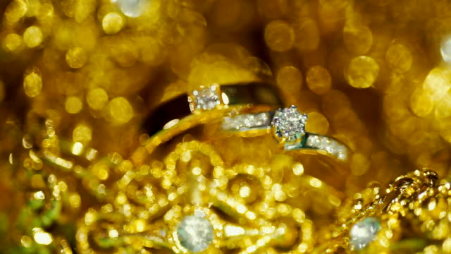 wedding rings with golden textured background. wedding theme. - argentato video stock e b–roll