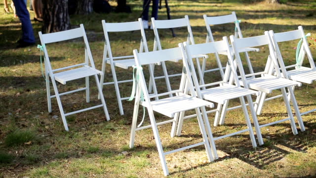 Wedding setup in garden, park. Outside wedding ceremony, celebration. Wedding aisle decor. Rows of white wooden empty chairs on lawn before the wedding ceremony. Slow pan video