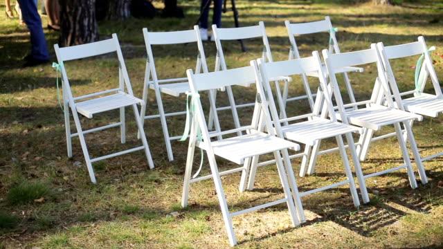 vidéos et rushes de configuration du mariage dans le jardin, parc. cérémonie de mariage extérieure, célébration. décoration de mariage de couloir. rangées de chaises vides en bois blanches sur la pelouse avant la cérémonie de mariage. pan lente - lieu sportif