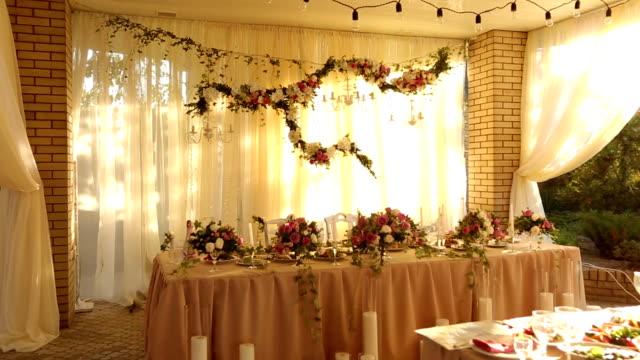 vídeos y material grabado en eventos de stock de boda decoración de estilo rústico mesa con platos, bebidas y flores en colores rosa y beige. composiciones florísticas de rosas en mesa de comedor de banquetes de fiesta - estilo de vida rural