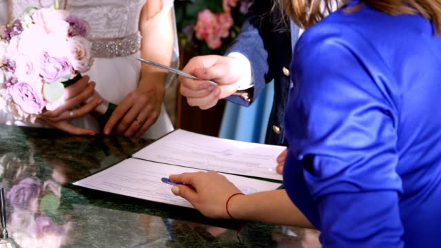 wedding traditions, ceremonies. wedding ceremony. newlyweds sign in marriage documents, marriage certificate. close-up
