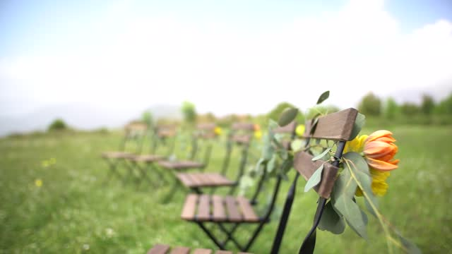 wedding venue, chairs decorated with flowers and eucalyptus branches