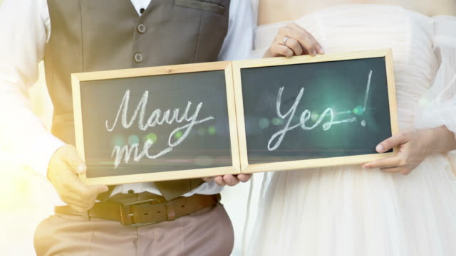 Weddings around the world. Wedding concept, will you marry me question and yes handwritten on blackboard.