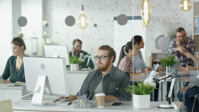 Weekday in a Busy Creative Bureau. Office People Working at Their Personal Computers, Talking on the Phone. Man Joins Coworkers at Conference Table Where Business Discussion is Taking Place. – Video