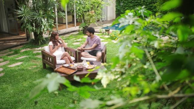 stockvideo's en b-roll-footage met weekend ontbijt en gesprek buitenshuis in de achtertuin - garden house