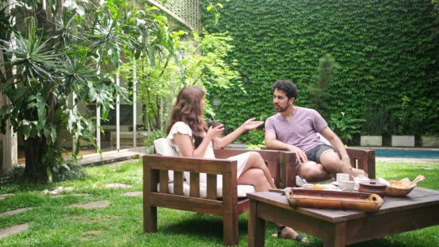 vídeos de stock, filmes e b-roll de café da manhã de fim de semana e conversa ao ar livre no quintal - mobília