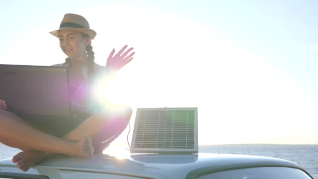 weekend since new technology, female sitting on car rooftop with notebook and battery on background sky in backlit video