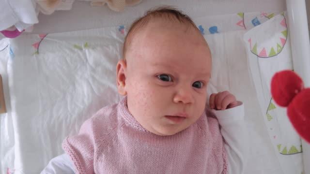 vidéos et rushes de vieux bébé de semaines se trouvant dans le lit avec les yeux ouverts - 0 11 mois