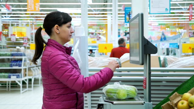süpermarket elektronik ölçeklerde elma tartım - pazarcı stok videoları ve detay görüntü çekimi