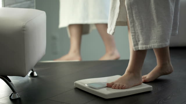Weight control, woman with some extra weight stepping on scales at home, dieting Weight control, woman with some extra weight stepping on scales at home, dieting stepping stock videos & royalty-free footage
