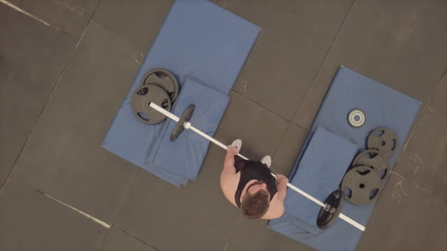 Weightlifting overhead press with barbell, aerial view video