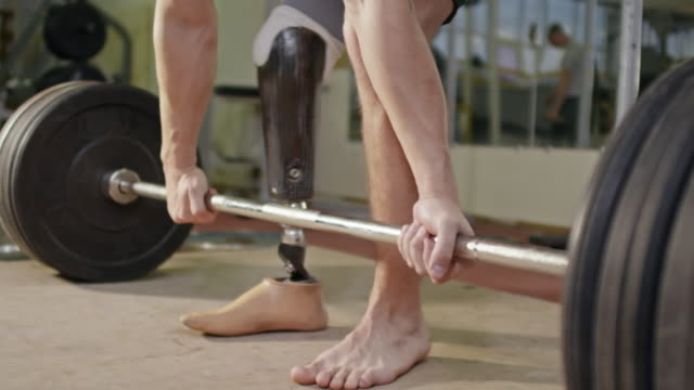 Weightlifting with Prosthetic Foot Closeup of male legs with one artificial foot lifting up barbell while training in gym on wooden floor amputee stock videos & royalty-free footage