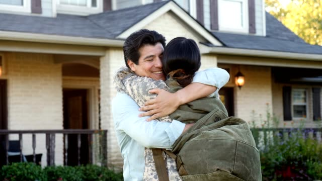 welcome home female military soldier family Slow motion video of mid adult Hispanic husband running to greet his wife upon her return from long military assignment. He picks her up as they rock back and forth. Their home is in the background. homecoming stock videos & royalty-free footage