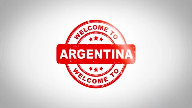 ¡Bienvenido a ARGENTINA había firmado sellado animación de madera sello de texto. Tinta roja en el fondo de superficie de papel blanco limpio con verde mate fondo incluido. - vídeo