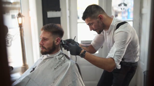 Welcome to best barber shop in your town! Barber giving a haircut in his shop hairstyle stock videos & royalty-free footage