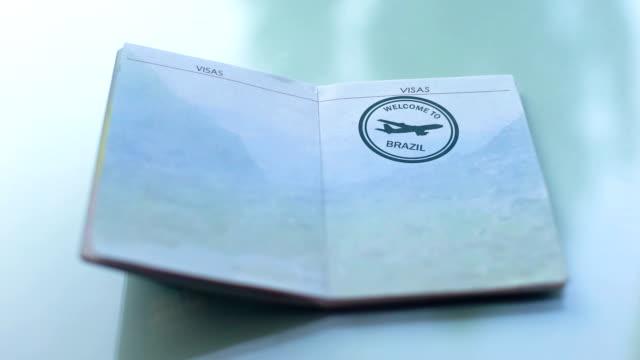 vídeos y material grabado en eventos de stock de bienvenido a brasil, costumbres oficial de mano estampado sello en el pasaporte, viajes - pasaporte y visa