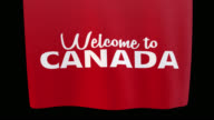 istock Welcome to Canada unfolding cloth sign. Alpha channel will be included when downloading the 4K Apple ProRes 4444 file only 1174707076
