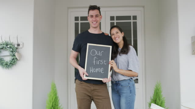 """Welcome to the neighbourhood 4K video footage of a happy young couple holding a sign with """"Our first home"""" written on it home ownership stock videos & royalty-free footage"""