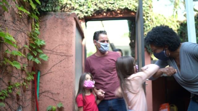 stockvideo's en b-roll-footage met het verwelkomen van vrienden thuis tijdens pandemie gebruikend gezichtsmasker en groet met elleboogstoot - sociale bijeenkomst