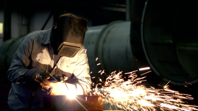 welder at work in metal fabrication shop - saldare video stock e b–roll