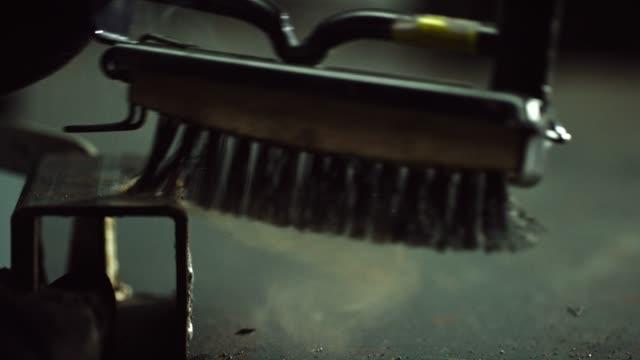 vidéos et rushes de un soudeur brosses loin copeaux de métal pendant le soudage dans un atelier - art et artisanat