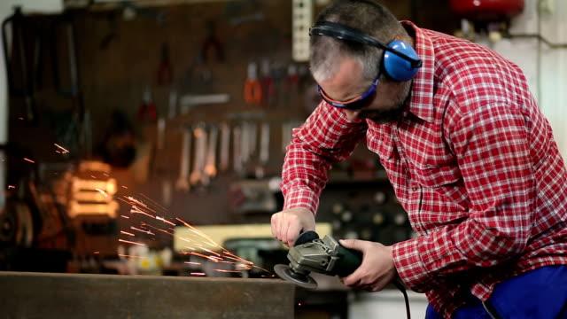 welder grinding metal plate at work - pinze attrezzo manuale video stock e b–roll