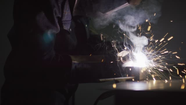 A Welder in Full Protective Gear Welds in a Workshop as Sparks Fly A Welder in Full Protective Gear Welds in a Workshop as Sparks Fly metalwork stock videos & royalty-free footage