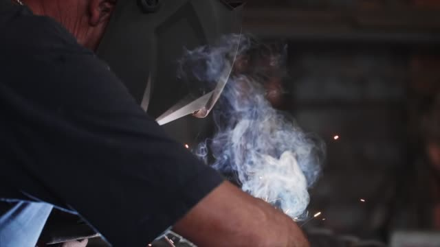 Welder in protective mask makes electric arc welding of metal in slow motion.