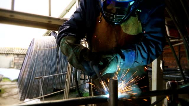 Welder in the workshop performs arc welding video