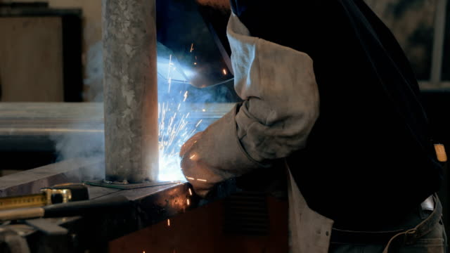 Welder welding metal parts in a workshop Welder welding metal parts in a workshop wearing a mask and protective gear metal worker stock videos & royalty-free footage