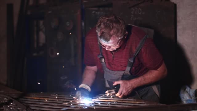 Welder welds metal fence in workshop without protective mask in slow motion.