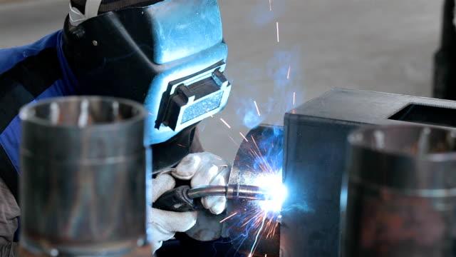 stockvideo's en b-roll-footage met welder lassen metalen onderdelen op een productielijn. - elektrisch gereedschap