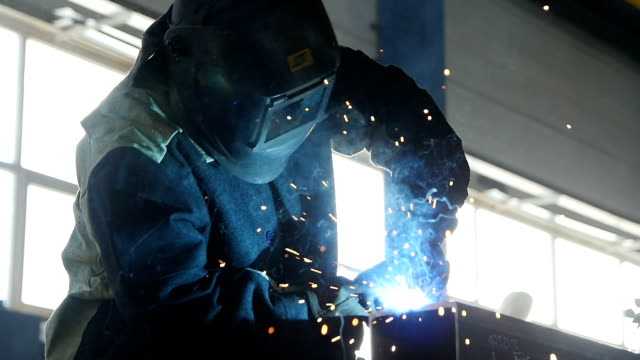 Welder Works Hard in Sparks Shower Clouseup Skilled welder in mask and protective suit works hard in sparks shower at factory shop clouseup metal worker stock videos & royalty-free footage