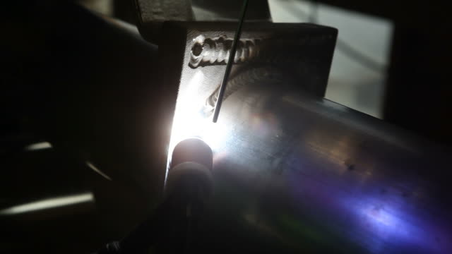 TIG Welding Aluminum Pipe A worker is using a TIG (Tungsten Inert Gas) welder to join an aluminum fitting to a pipe. This is the second pass, creating a very study weld. Partway through the clip the piece is rotated without stopping the welding process. pipefitter videos stock videos & royalty-free footage